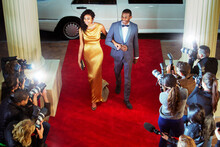 Celebrity Couple Arriving At Red Carpet Event Being Photographed By Paparazzi