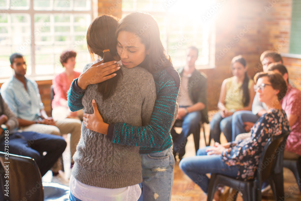 Fototapeta Women hugging in group therapy session