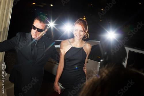 Bodyguard escorting smiling celebrity arriving at event Tableau sur Toile