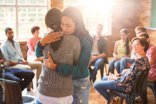 Fotografiet Women hugging in group therapy session