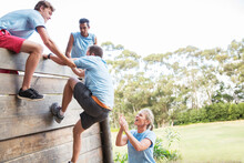 Teammates Helping Man Over Wall On Boot Camp Obstacle Course