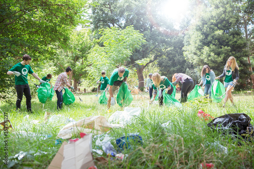 Environmentalist volunteers picking up trash in field Fototapeta