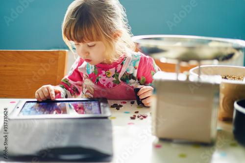 Curious girl using digital tablet Fototapeta