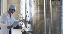 Vintner In Lab Coat Hard Hat Examining Stainless Steel Vat In Cellar