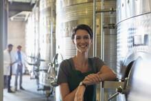 Portrait Smiling Vintner At Stainless Steel Vat In Winery Cellar