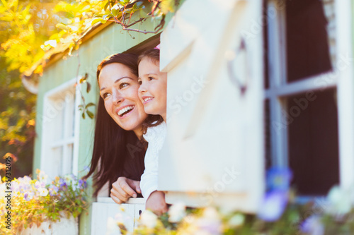 Fotografia, Obraz Smiling mother and daughter in playhouse window