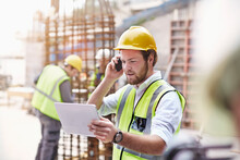 Engineer Digital Tablet Talking On Cell Phone At Construction Site