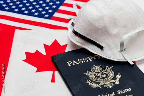 Flags of Canada and America, passport and N95 respirator mask Fototapeta