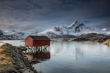 Snow Covered Mountains Behind Fishing Hut Over Lake, Sund, Lofoten Islands, Norway