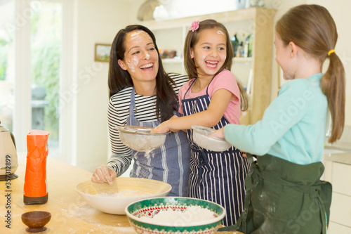 Photo Laughing mother and daughters baking with flour on faces in kitchen