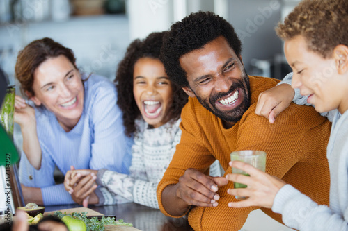 Obraz Laughing family drinking healthy green smoothie in kitchen - fototapety do salonu