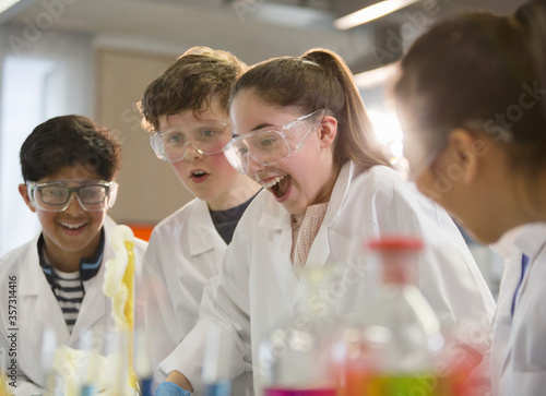 Obraz Surprised students conducting exploding foam scientific experiment in classroom laboratory - fototapety do salonu