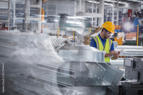 Fotografie, Obraz Factory worker with clipboard inspecting steel parts in factory