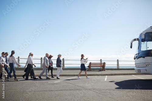 Fotografija Tour guide leading active senior tourists to tour bus