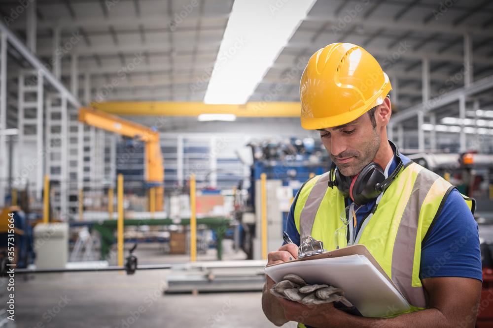 Fototapeta Male worker writing on clipboard in factory