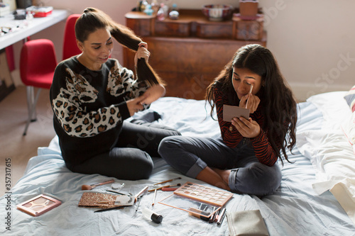 Teenage girls applying makeup and brushing hair on bed Canvas Print