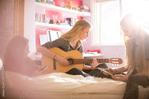 Fotografie, Obraz Teenage girls playing guitar and using digital tablet on bed