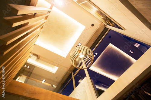 Fotografie, Obraz Illuminated tray ceiling and modern pendant light hanging in luxury foyer