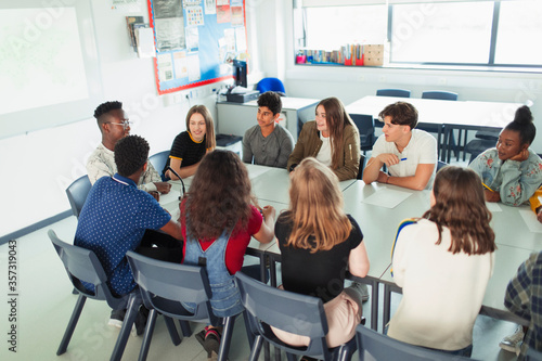 Foto High school students talking in debate class at table in classroom