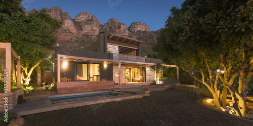Mountains behind illuminated modern, luxury home showcase exterior house at nigh Canvas Print