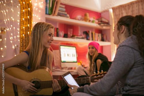 Fotografia, Obraz Teenage girls playing guitar and using digital tablet in bedroom