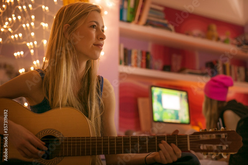 Teenage girl playing guitar in bedroom Fototapet