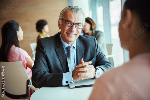 Smiling businessman listening to colleague in cafeteria Canvas Print