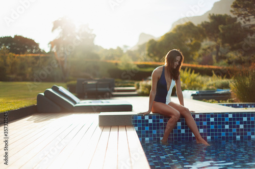 Fotografiet Woman in bathing suit relaxing at luxury swimming pool