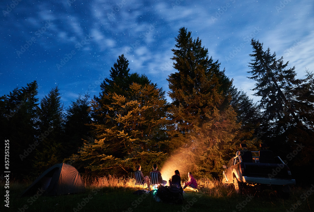 Fototapeta Night starry sky over meadow with travelers near campfire. Tourists resting in the wood with tall coniferous trees, car and camp tent under blue sky. Concept of travelling and night camping. - obraz na płótnie