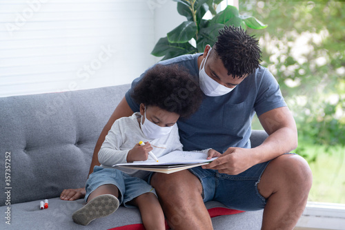 Fotografia African father and son with protective masks drawn picture together on couch, pr