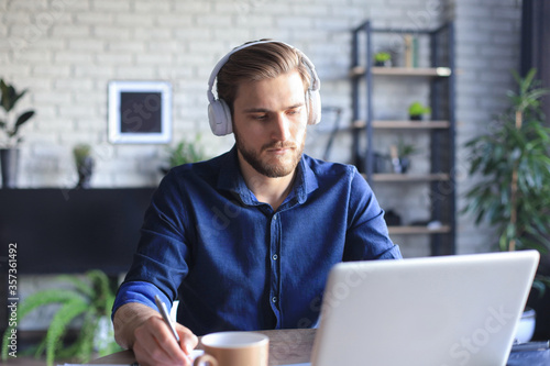 Fototapeta Confident businessman in earphones is writing notes or financial report while sitting at desk with laptop at home. obraz