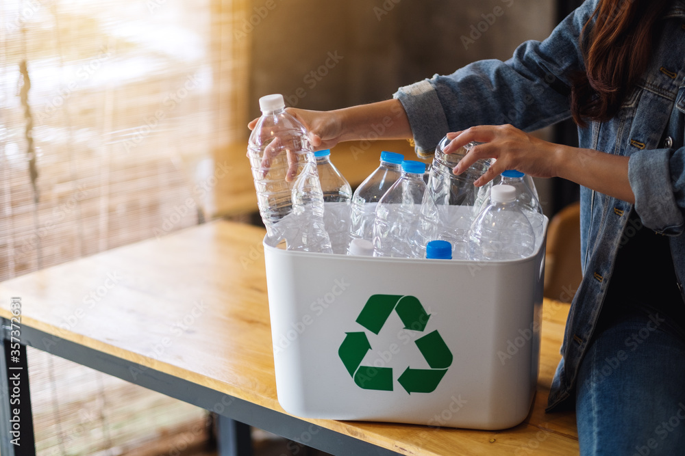 Fototapeta A woman collecting and separating recyclable garbage plastic bottles into a trash bin at home
