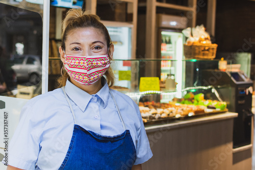 waitress with a face mask at the entrance of the cafeteria Fotobehang
