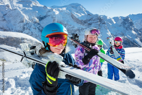 Fotomural Portrait of a girl hold ski on shoulder with group of children friends in vivid