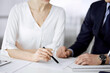 Unknown businessman and woman discussing contract in office. closeup.Business people or lawyers working together at meeting. Teamwork and partnership