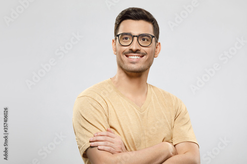 Fotografiet Portrait of young handsome guy dressed in beige t-shirt and wearing eyeglasses,