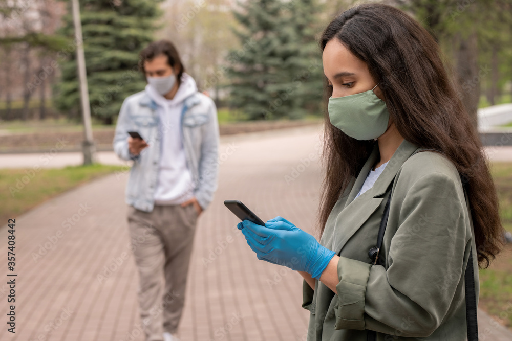 Fototapeta Young woman in green mask and gloves standing in city park and texting sms on smartphone, social distancing during coronavirus concept