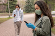 Young woman in green mask and gloves standing in city park and texting sms on smartphone, social distancing during coronavirus concept