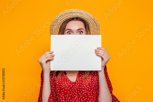 Fototapeta A young shocked girl in a summer red dress, a straw hat, holds an A4 empty poster and covers her face. Surprised woman shows a poster, canvas, white sheet of paper isolated over orange background obraz