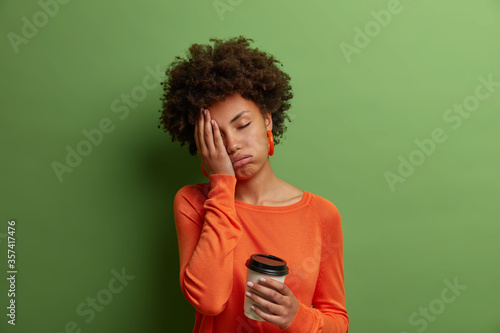 Cuadros en Lienzo Sleepy exhausted dark skinned curly woman holds cup of coffee, cannot wake up an