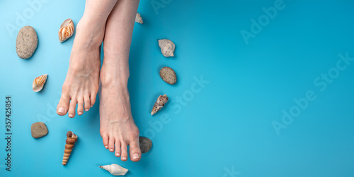 Fotografía Beautiful women's feet with beige nail polish on a blue background with seashells