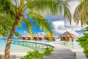 Fototapeta Egzotyczne Luxury water villas bungalows in the Maldives islands, sunny hot weather as blue sky and white clouds. Idyllic and exotic scenery, jetty over blue lagoon. Summer holiday and beach vacation concept