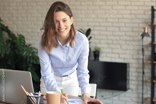 Confident young businesswoman with a friendly smile standing behind her desk in a home office looking at the camera.