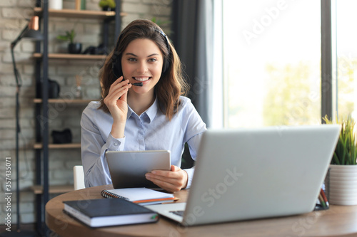 Obraz Freelance operator talking with headsets and consulting clients from home office. - fototapety do salonu