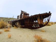 Rusty Timbers Of Sea Ship On The Former Bottom Of Dried Aral Sea, Zone Of Ecological Catastrophe, Now Popular For Extreme Travels. Picture Taken In Ex Sea Port Mo'ynoq (Moynaq) Or Muynak, Uzbekistan