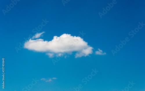 Fototapeta a white fluffy light cloud in the blue summer sky