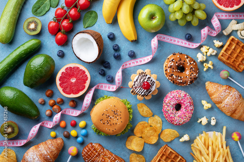 Fotografie, Obraz Healthy and unhealthy food background from fruits and vegetables vs fast food, sweets and pastry top view
