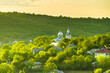 Leinwandbild Motiv Fresh morning rural landscape with greenery surrounding houses and a church on the hill top