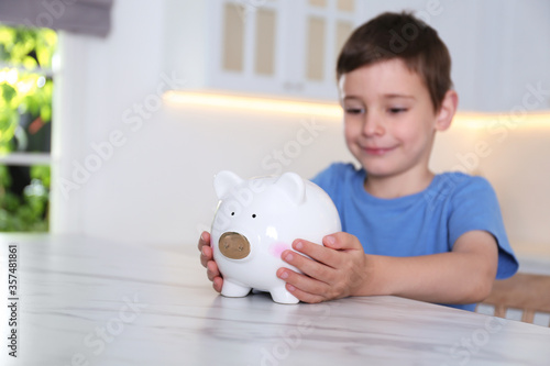 Fotografía Little boy with piggy bank at marble table indoors