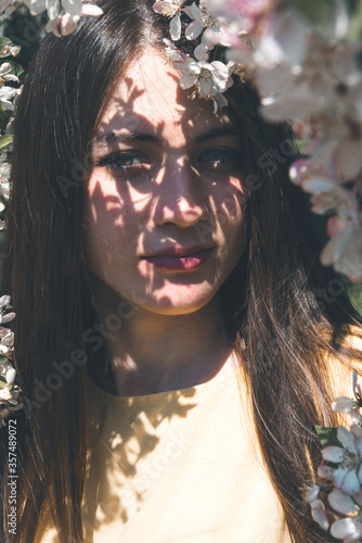 1 white young woman with long hair among Apple blossoms, shadow of flowers on her face